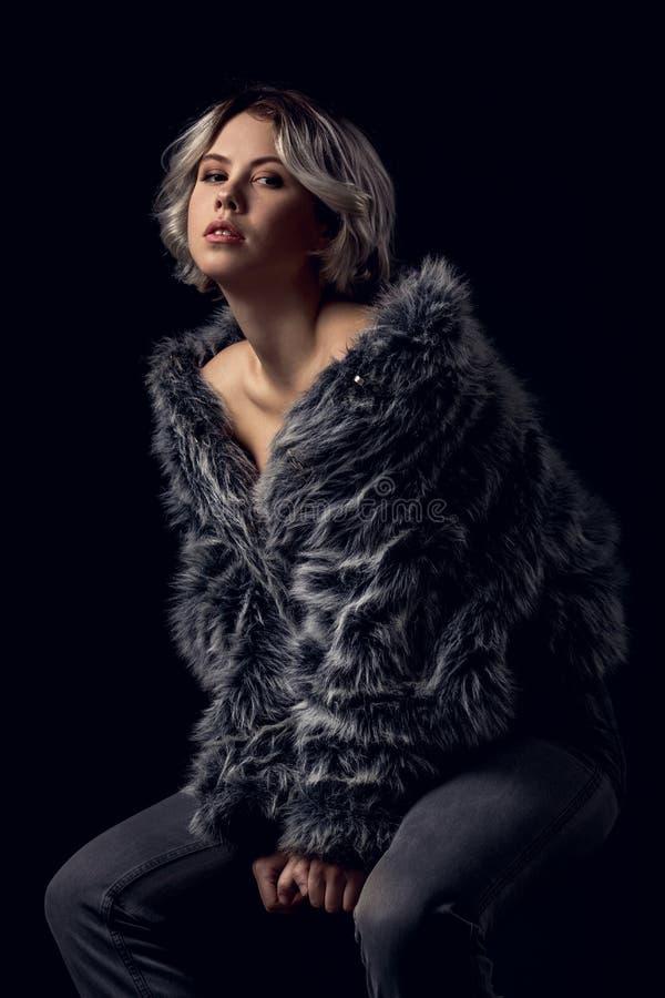 Luxusart der jungen Frau lokalisiert auf der grauen Wand, die auf Stuhl sitzt stockfotos