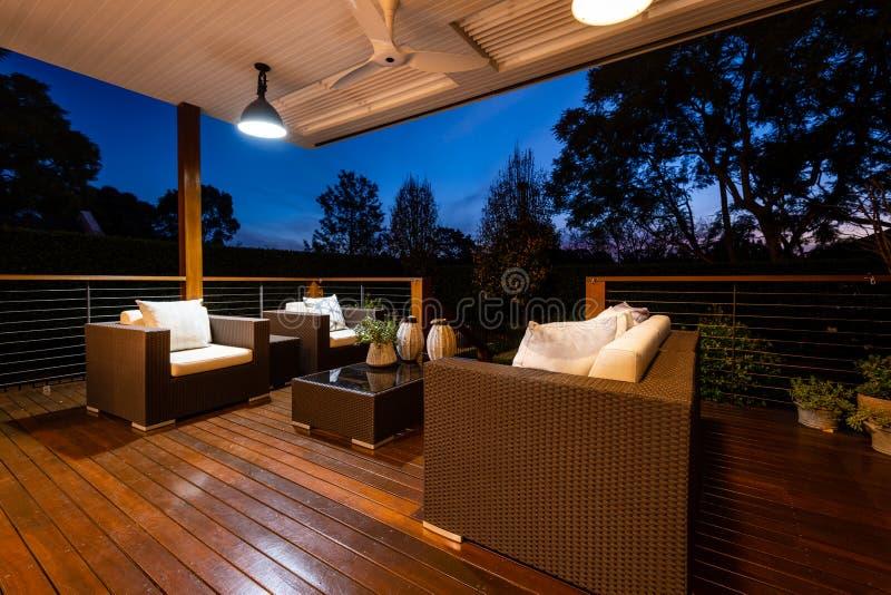 Luxusaufenthaltsraumbereich im Freien mit den Stühlen und Kissen, die in der Dämmerung auf schönen Garten von einer Plattform, Sc stockfotos