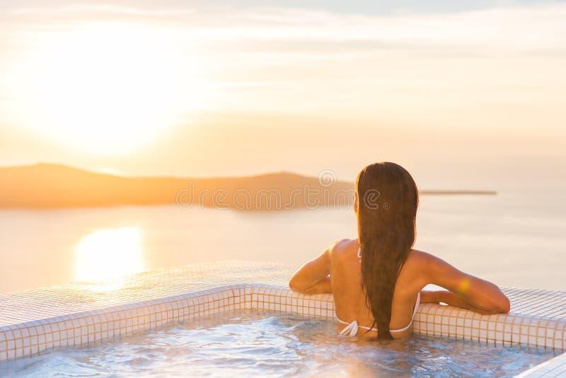 Luxusbadekurort Wellness-Erholungsortfrau, die in aufpassendem Sonnenuntergang des Jacuzzis der heißen Wanne über dem Ägäischen M lizenzfreie stockfotografie