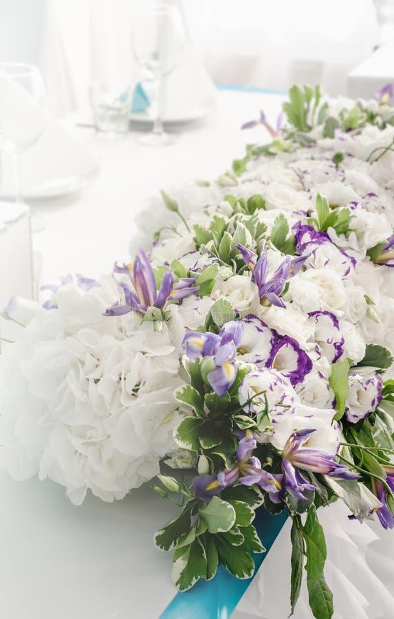 Luxusbankettisch mit reicher Dekoration von üppigen Blättern der Blumen, weiße Hortensie, Sahnerosen, purpurroter Eustoma, blau stockfotografie