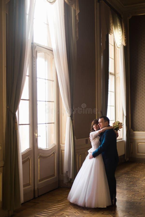 Luxusbraut und hübscher Bräutigam, die am herrlichen Fenster auf dem Hintergrund des reichen Innenraums im Altbau umarmt stockfotografie
