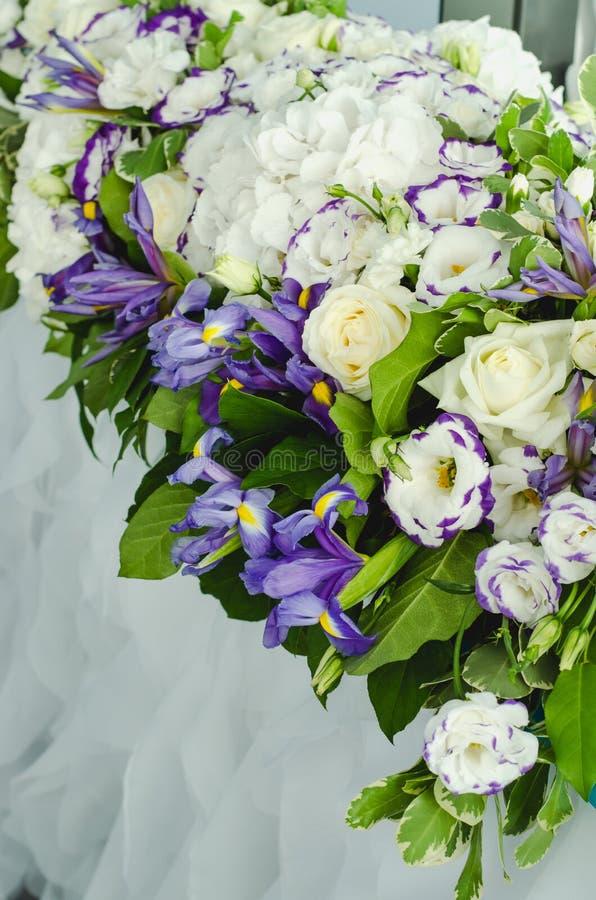 Luxusdekoration mit Stoff verlässt, weiße Hortensie, empfindliche Sahnerosen, purpurroter Eustoma, blaue Iris auf einer Hochzeits lizenzfreies stockbild