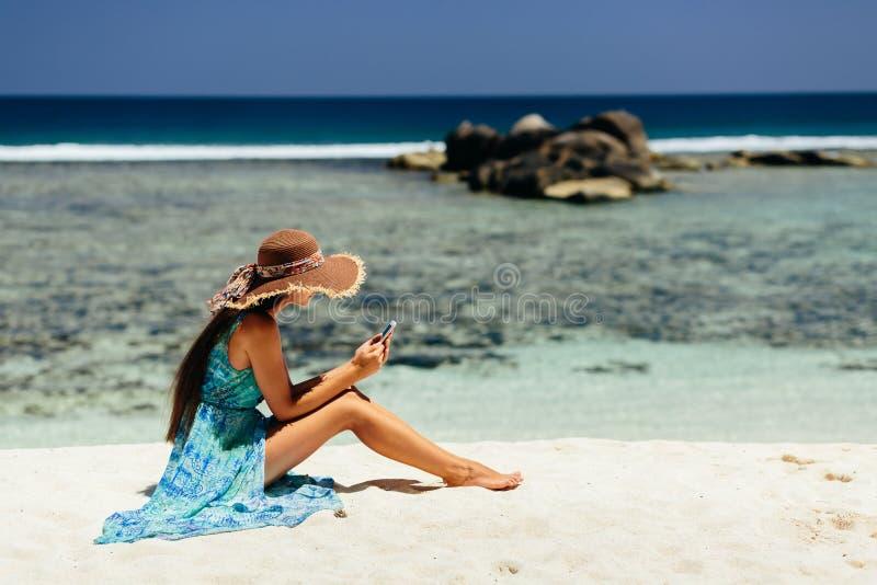 Luxusfrau, die Smartphone auf Strand verwendet stockfoto