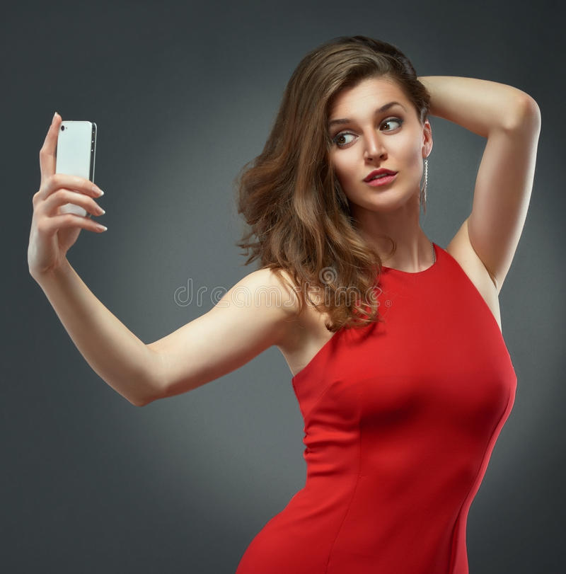 Luxusfrau im roten Kleid, das telefonisch selfie Foto macht lizenzfreie stockfotos