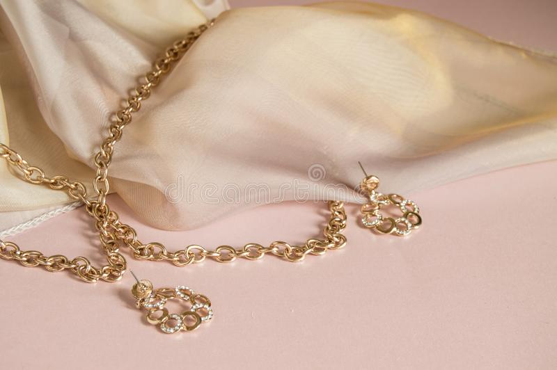Luxusgoldschmuckkette und -ohrringe auf rosa Hintergrund mit Seide, Kopienraum, selektiver Fokus lizenzfreie stockbilder