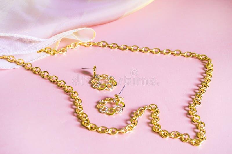 Luxusgoldschmuckkette und -ohrringe auf rosa Hintergrund mit Seide, Kopienraum, selektiver Fokus lizenzfreie stockfotografie
