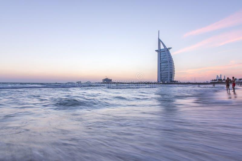 Luxushotel Burj Al Arab und Öffentlichkeit setzen bei Sonnenuntergang auf den Strand Dubai, UAE - 29/NOV/2016 lizenzfreie stockfotografie