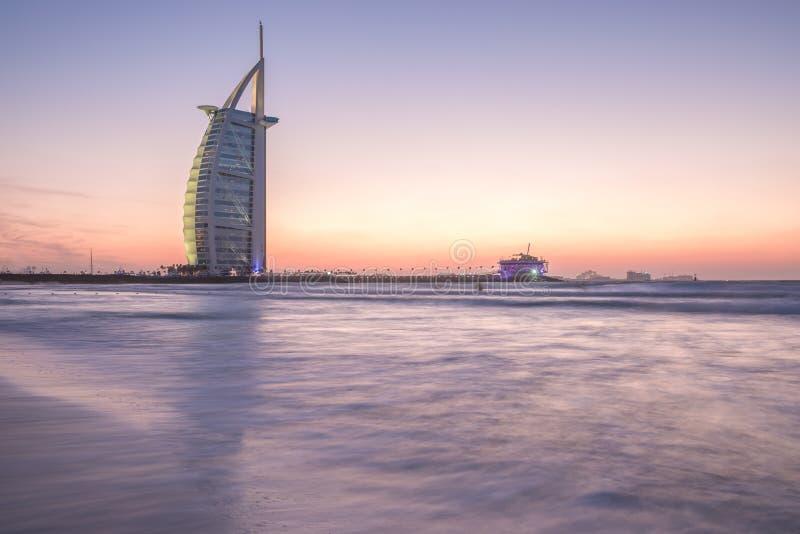 Luxushotel Burj Al Arab und Öffentlichkeit setzen bei Sonnenuntergang auf den Strand Dubai, UAE - 29/NOV/2016 stockfoto