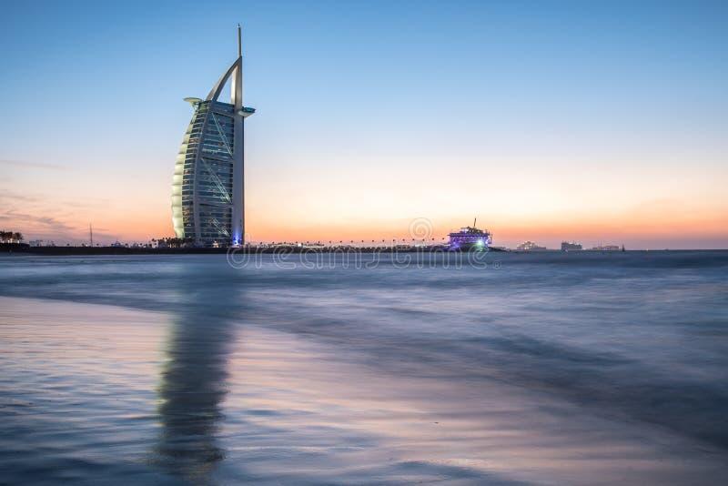 Luxushotel Burj Al Arab und Öffentlichkeit setzen bei Sonnenuntergang auf den Strand Dubai, UAE - 29/NOV/2016 lizenzfreies stockfoto