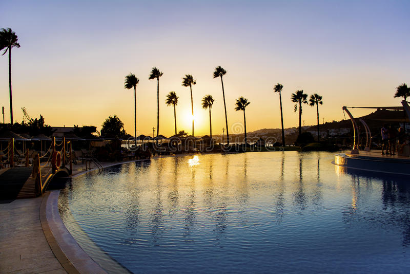 LuxushotelSwimmingpool mit Palmen bei Sonnenuntergang stockfotografie