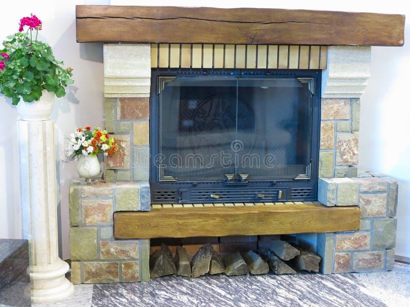 Luxuskamin mit Brennholz- und Blumenvasendekorationen stockbild