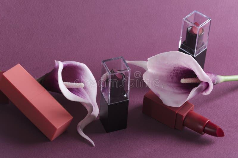 Luxuslippenstifte und purpurrote Callas auf dem violetten Hintergrund stockbilder