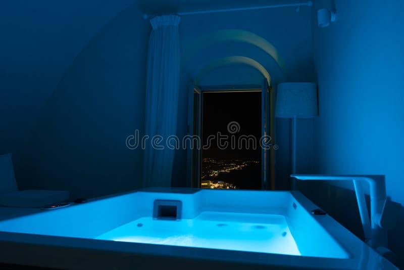 Luxusreise Santorini-Ferien-Hoteljacuzzi in farbigen Lichtern mit Nachtansicht der Stadt stockfotografie
