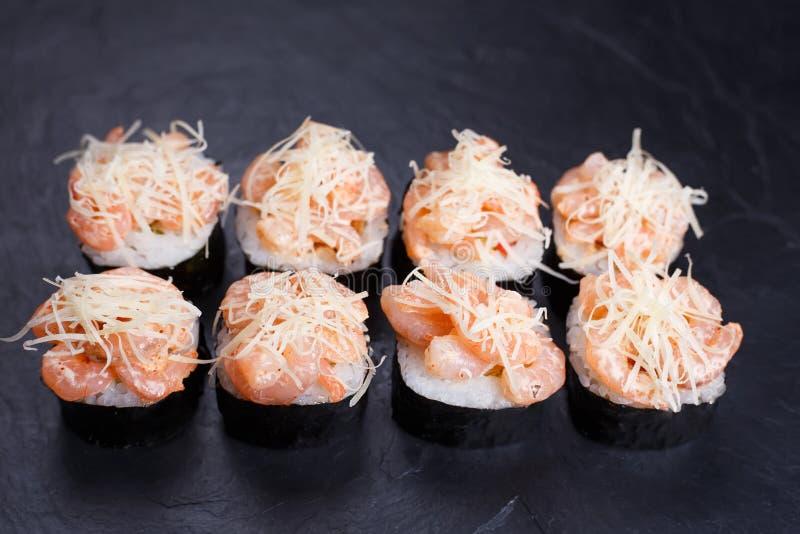 Luxusrestaurantsushimenü Sushirollen verziert mit Garnelen lizenzfreie stockbilder