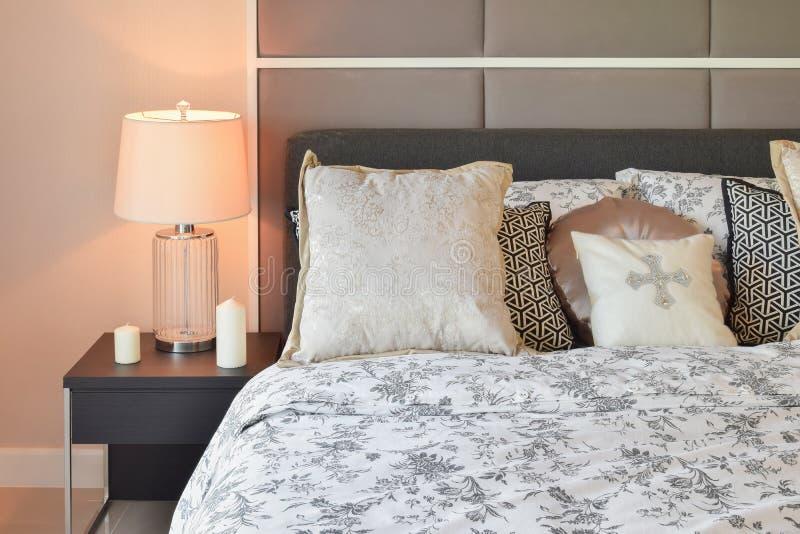 Luxusschlafzimmer mit Blumenmusterkissen und dekorativer Tischlampe lizenzfreies stockbild