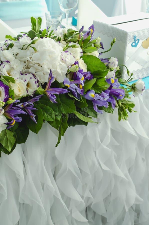 Luxustabelle schön, reiche Dekoration mit üppigen Blättern, weiße Hortensie, empfindliche Sahnerosen, purpurroter Eustoma, blau stockfotos