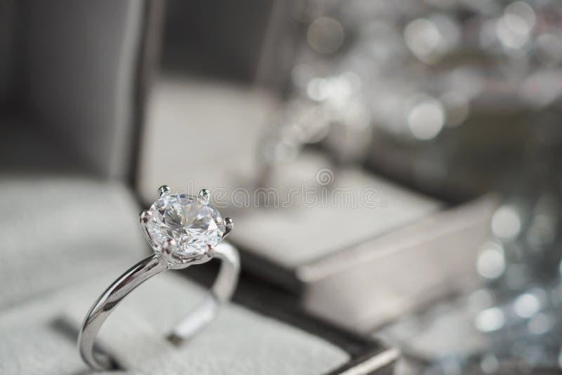 Luxusverpflichtung Diamantring in der Schmuckgeschenkbox mit bokeh lizenzfreie stockfotografie