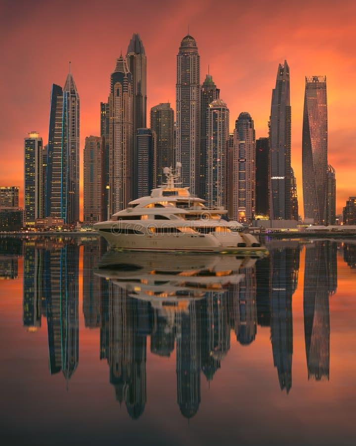Luxusyacht vor Skylinen an Dubai-Jachthafen auf idyllischem Sonnenuntergang lizenzfreies stockbild