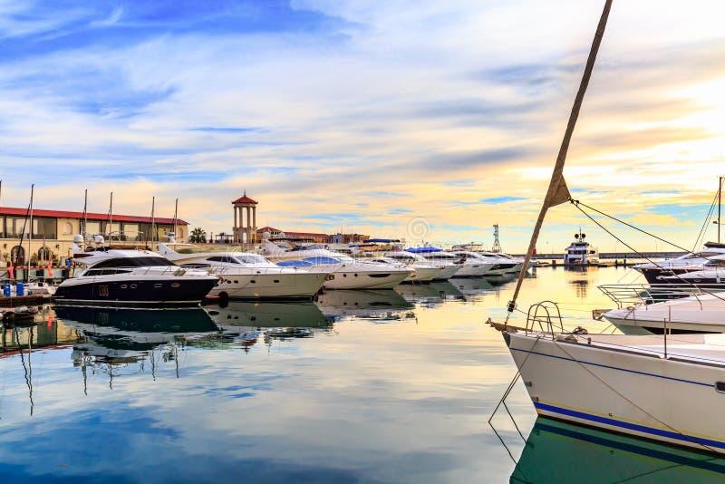 Luxusyachten, Motor und Segelboote koppelten im Jachthafen bei Sonnenuntergang an stockfotos