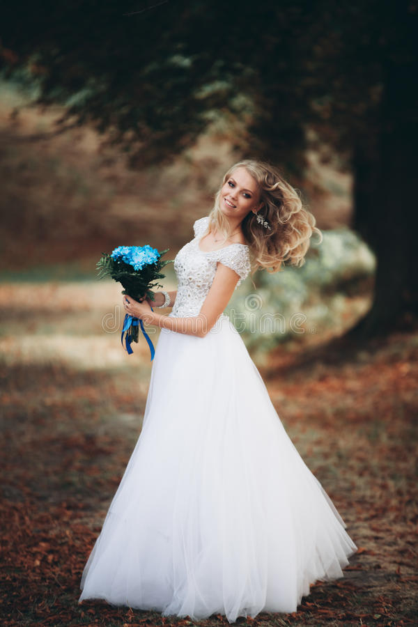 Luxuty portrait of blonde bride with bridal bouquet in autumn royalty free stock photography
