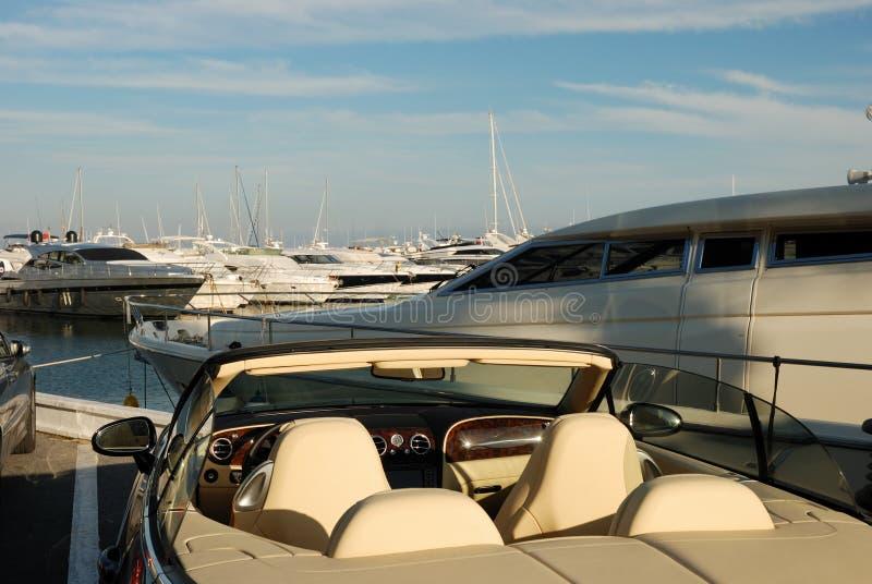 Luxuxauto und Yachten stockbild