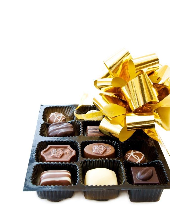 Luxuxschokoladen und festliche goldene Farbbänder stockbilder