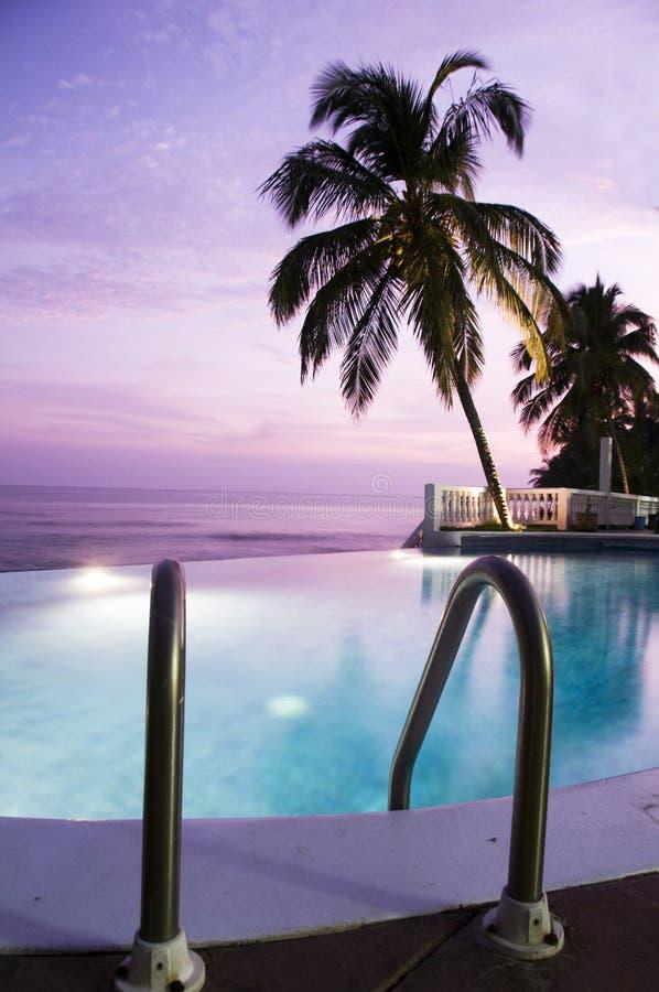 LuxuxunbegrenztheitsSwimmingpool-Meer-Sonnenuntergang stockbild