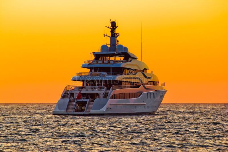 Luxuxyacht auf hoher See am Sonnenuntergang lizenzfreie stockbilder