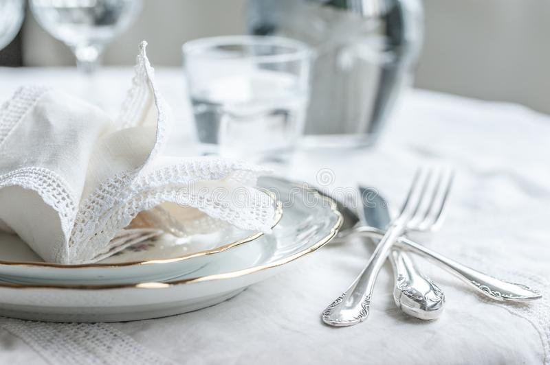 Luxyry dinner set arranged on a table with vintage lace tablecloth and napkins, elegant porcelain dishes, silverware and crystal. Luxyry dinner set arranged on a royalty free stock photography