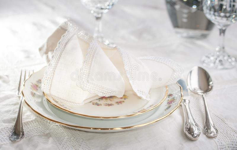 Luxyry dinner set arranged on a table with vintage lace tablecloth and napkins, elegant porcelain dishes, silverware and crystal. Luxyry dinner set arranged on a royalty free stock photos