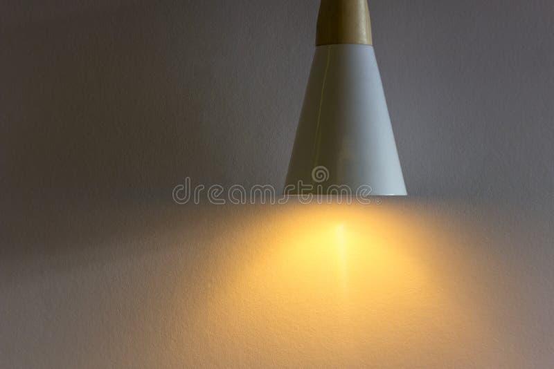 Luz ámbar brillante de una lámpara en una pared gris blanca granosa con las sombras Textura de la superficie ?spera imagen de archivo