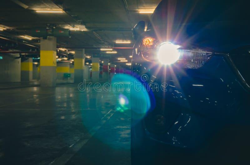 Luz abierta de la linterna del coche de SUV y parqueado en el aparcamiento de subterráneo de las compras Estacionamiento de la al foto de archivo