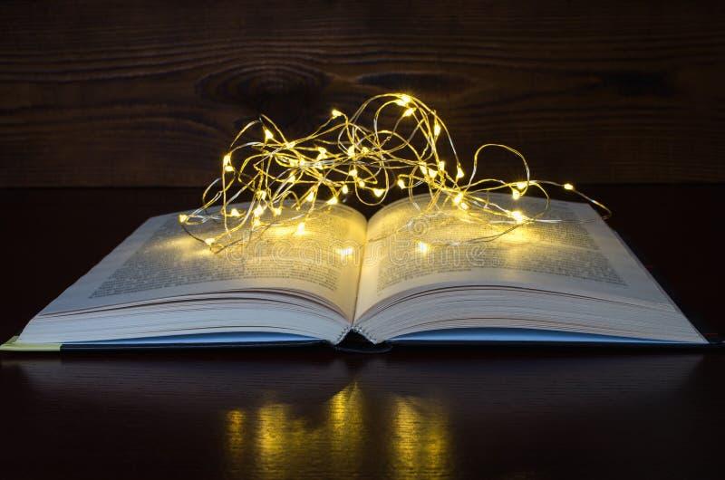 Luz abierta del libro de una guirnalda en el de madera oscuro foto de archivo
