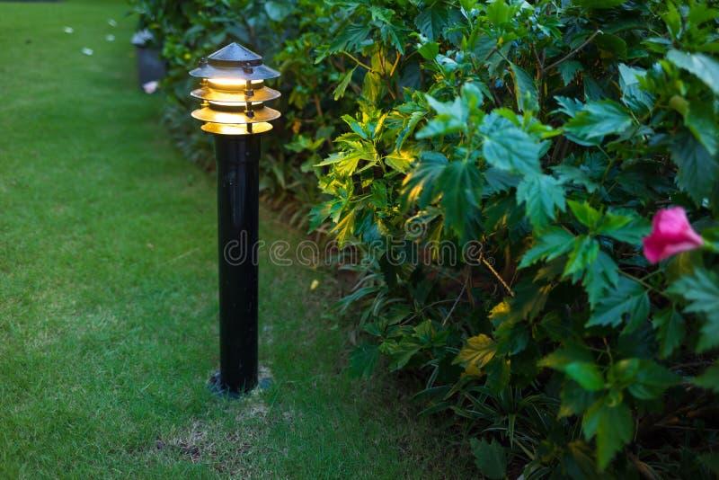 Luz al aire libre iluminada en jardín del apartamento en el crepúsculo, igualando imagen de archivo