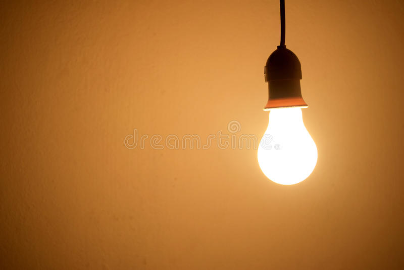 Luz alaranjada da lâmpada da ampola na sala na noite fotografia de stock