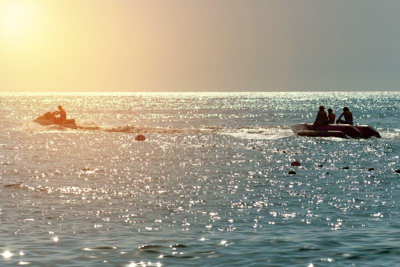 Luz alaranjada de c?u azul no por do sol a silhueta de um esqui do jato do barco de banana tem o divertimento fotos de stock royalty free