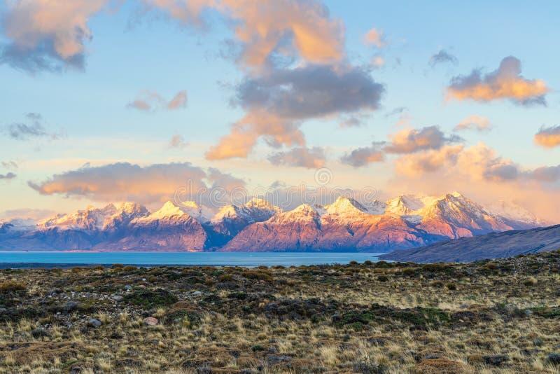 Luz alaranjada dourada do alvorecer bonito da elevação do sol sobre a montanha da neve com o lago azul profundo na manhã com nuve fotos de stock