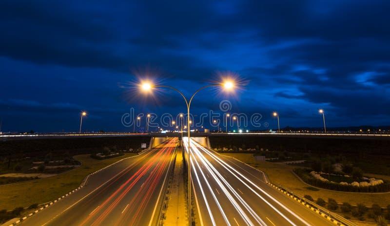 A luz arrasta dos carros moventes rápidos em uma estrada imagem de stock