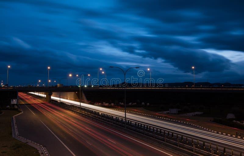 A luz arrasta dos carros moventes rápidos em uma estrada fotografia de stock royalty free