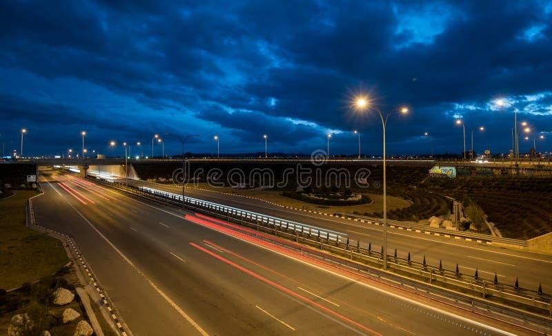 A luz arrasta dos carros moventes rápidos em uma estrada fotos de stock royalty free