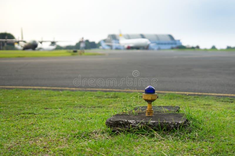 Luz azul da borda da segurança ao lado do Taxiway do aeroporto com o avião do borrão no fundo fotos de stock royalty free