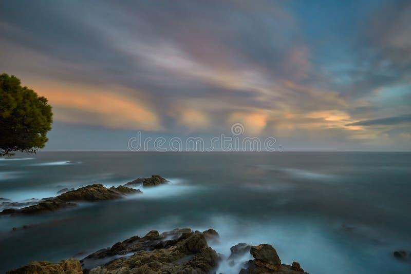 Luz bonita do por do sol em Costa Brava da Espanha, perto da cidade Palamos, imagem longa da exposição fotos de stock royalty free