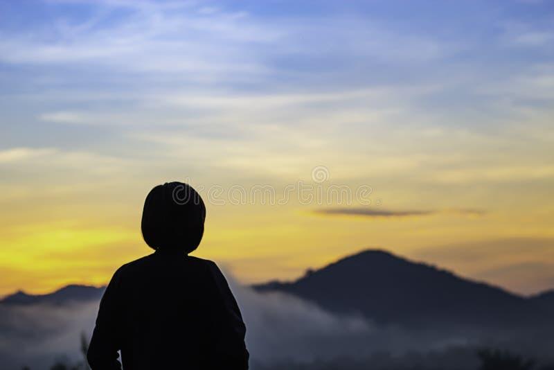 Luz borrosa del sol de la mañana detrás de las montañas con la sombra de una mujer y de la niebla fotografía de archivo libre de regalías