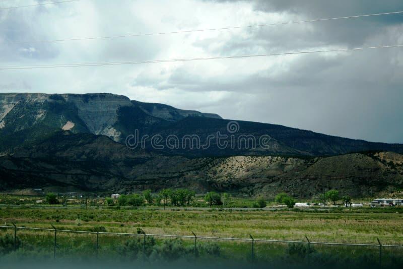 A luz cai belamente nas montanhas verdes e cinzentas através das nuvens do céu Estado de Colorado foto de stock royalty free
