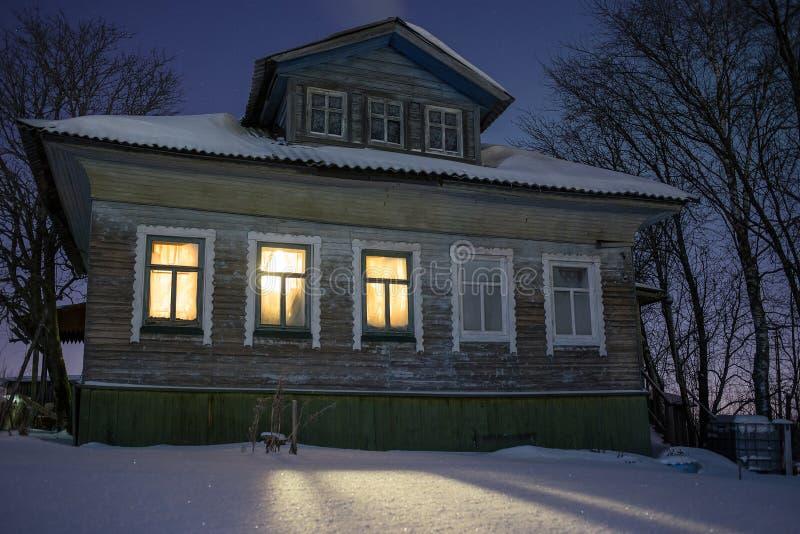 Luz caliente de la casa rusa vieja ofcozy del pueblo de las ventanas en el frío punzante Paisaje de la noche del invierno con nie imagenes de archivo