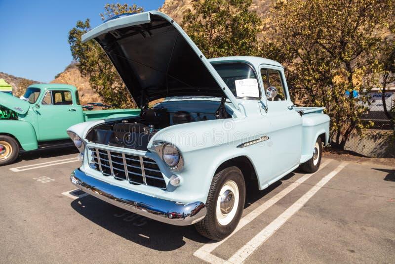 Luz - caminhão 1955 grande da janela de Chevrolet 3100 azuis imagem de stock royalty free