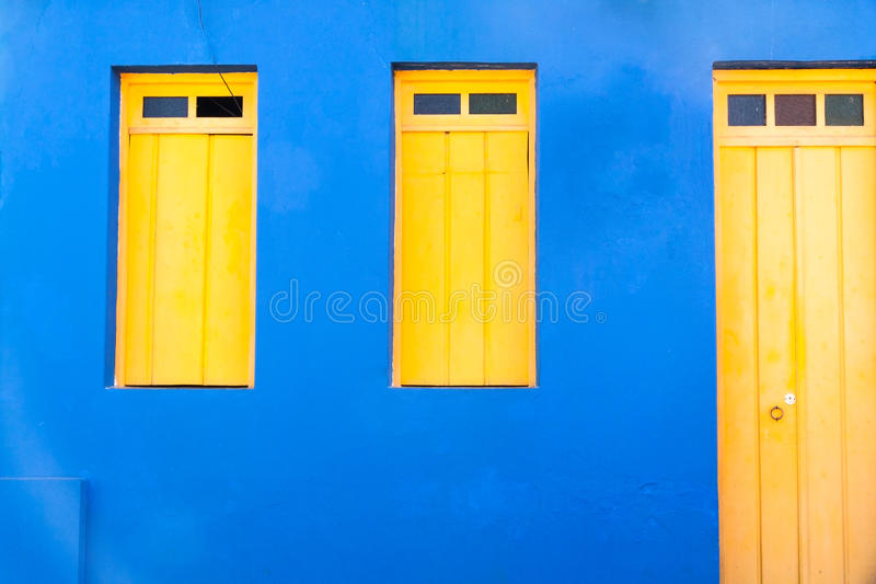 Luz colorida das caraíbas - fachada azul com a porta amarela brilhante e o Windows imagens de stock royalty free
