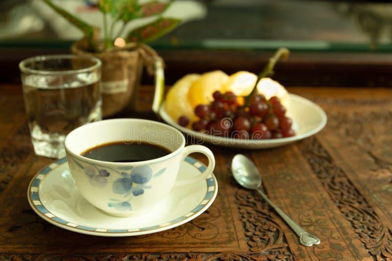 Luz da manhã com copo de café e vidro da água e do fruto fresco foto de stock royalty free