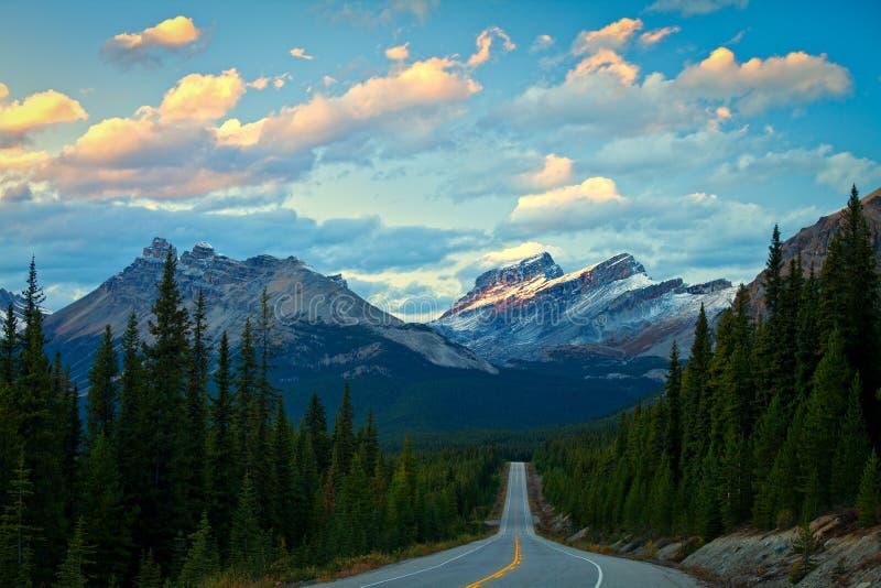 Luz da noite nas montanhas ao longo da via pública larga e urbanizada de Icefields no parque nacional de Banff foto de stock