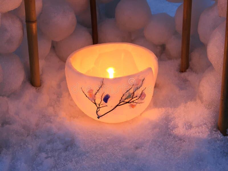 Luz da vela em um fundo da bacia do gelo fotografia de stock royalty free